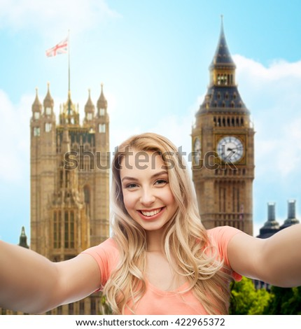 travel, tourism, emotions, expressions and people concept - happy smiling young woman taking selfie over big ben london and city background - stock photo