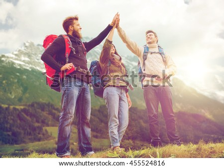 travel, tourism, hike, gesture and people concept - group of smiling friends with backpacks making high five over alpine mountains and hills background - stock photo