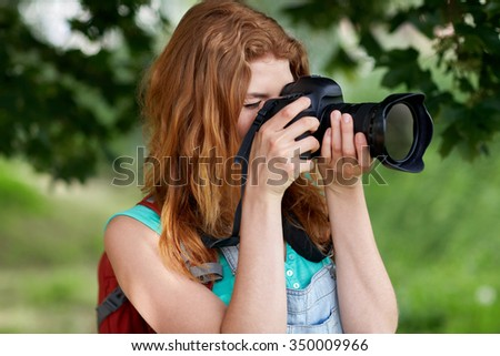 travel, tourism, hike, hobby and people concept - young woman with backpack and camera photographing outdoors - stock photo
