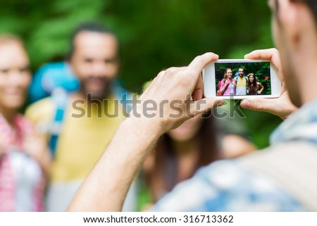 travel, tourism, hike, technology and people concept - close up of man photographing friends with backpacks by smartphone outdoors - stock photo