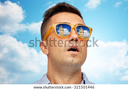 travel, tourism, sightseeing, emotions and people concept - face of man in sunglasses looking at big ben tower over blue sky and clouds background