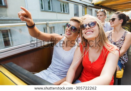 travel, tourism, summer vacation, sightseeing and people concept - happy teenage couple in sunglasses traveling by tour bus and listening to music with earphones - stock photo
