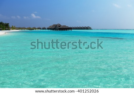 travel, tourism, vacation and summer holidays concept - bungalow huts in sea water on exotic resort beach - stock photo