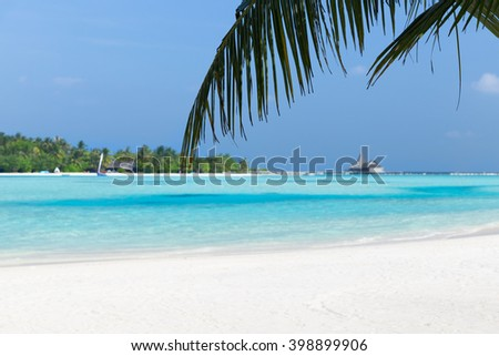 travel, tourism, vacation and summer holidays concept - maldives island beach with palm tree and villa - stock photo