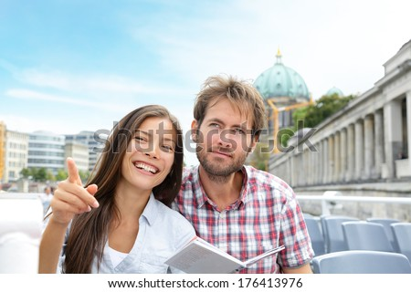 Travel tourist couple on boat tour in Berlin, Germany having fun smiling happy while enjoying romance on Europe travel vacation holiday. Asian woman, Caucasian man. - stock photo