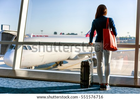 Travel tourist standing with luggage watching sunset at airport window. Unrecognizable woman looking at lounge looking at airplanes while waiting at boarding gate before departure. Travel lifestyle.