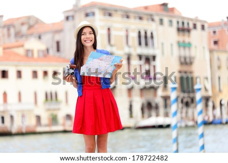 Travel tourist woman with camera and map in Venice, Italy. Asian girl on vacation smiling happy by Grand Canal. Mixed race Asian Caucasian girl having fun traveling outdoors during holidays in Europe. - stock photo