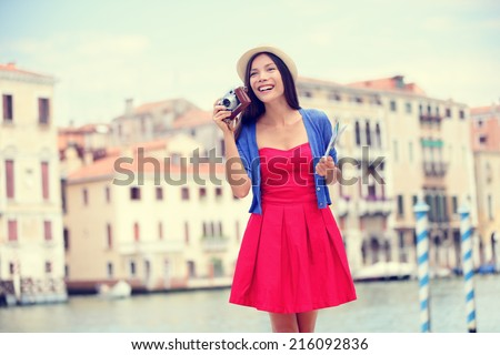 Travel tourist woman with camera and map in Venice, Italy. Vintage retro style Asian girl on vacation smiling happy by Grand Canal. Mixed race Asian Caucasian girl having fun traveling outdoors. - stock photo