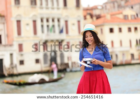Travel tourist woman with camera and map in Venice, Italy. Vintage retro style Asian girl on vacation smiling happy by Grand Canal. Mixed race Asian Caucasian girl in fashion red dress. - stock photo
