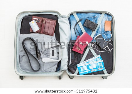 travel traveler traveling bag top open view packing card camera packed credit wallet clothing table leaving departure concept