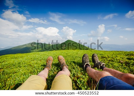 Travel trekking leisure holiday concept. Couple in hiking boots having fun and enjoying wonderful breathtaking mountain view - stock photo