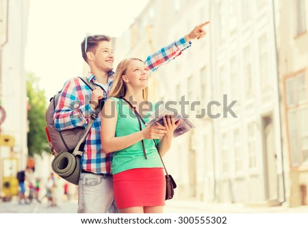 travel, vacation and friendship concept - smiling couple with city guide and backpack in city - stock photo