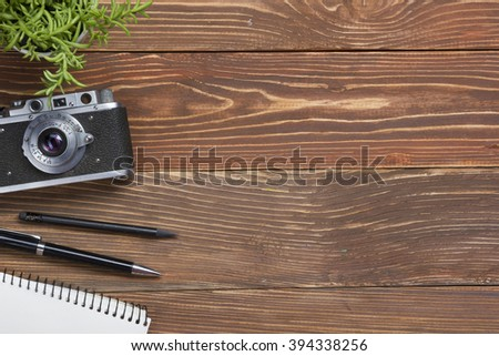 Travel, vacation concept. Camera and supplies on office wooden desk table. Top view with copy space for text - stock photo