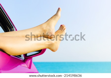 Travel vacation freedom beach concept. Female legs out of car window. - stock photo