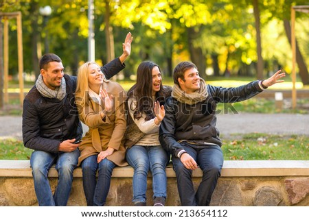 travel, vacation, people, gesture and friendship concept - group of smiling friends waving hands in city park - stock photo