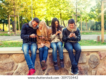travel, vacation, people, technology and friendship concept - group of smiling friends with smartphones in city park