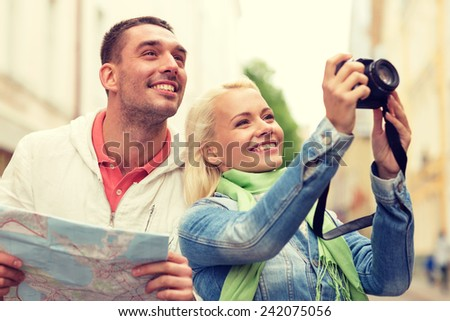 travel, vacation, technology and friendship concept - smiling couple with map and photocamera exploring city - stock photo