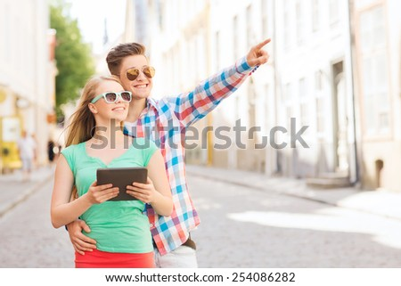 travel, vacation, technology and friendship concept - smiling couple with tablet pc computer in city - stock photo