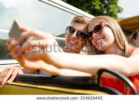 travel, vacation, technology, summer and people concept - smiling couple with smartphone traveling by tour bus and making selfie - stock photo