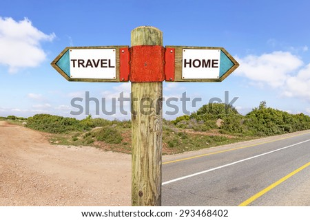 Travel versus Home messages - Wooden signpost with two opposite arrows on a road intersection with nature landscape in the background. Choice chance and change of lifestyle conceptual image  - stock photo