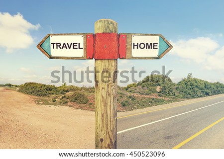 Travel versus Home messages. Wooden signpost with two opposite arrows on a road intersection with nature landscape in the background. Choice and change conceptual image. Toned colors