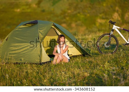Travel with bicycle alone - young slim sportive woman brunette tourist at the beautiful nature landscape laying near the tent