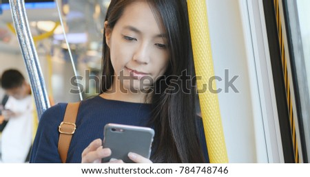 Travel Woman using cellphone in train compartment, busy life style of human life in Hong Kong