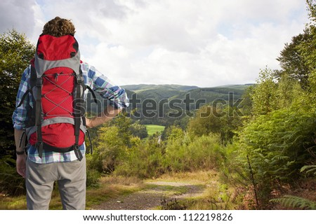 Traveler absorbing the view of the Belgium Ardennes, as he clears the woods on top of a hill - stock photo