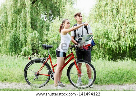 traveler asks for directions from a cyclist - stock photo
