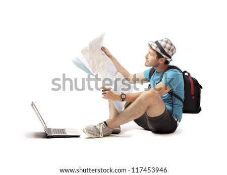 Traveler boy checking out a map with the aid of a laptop computer - stock photo