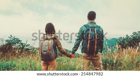 Traveler couple in love enjoying view of sea and holding hands each other. Image with instagram filter - stock photo