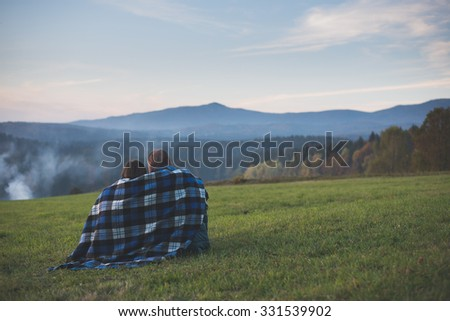 Traveler couple watching landscape and mountains under a blanket - stock photo