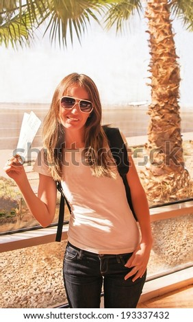 Traveler girl is near the airport window. Passenger woman with backpack and air ticket is in terminal. Air travel concept with happy female, who standing with hand luggage (Sharm El Sheikh, Egypt).   - stock photo