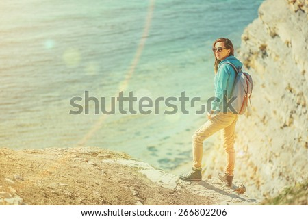 Traveler girl with backpack walking on coastl near the sea in summer. Image with sunlight effect. - stock photo