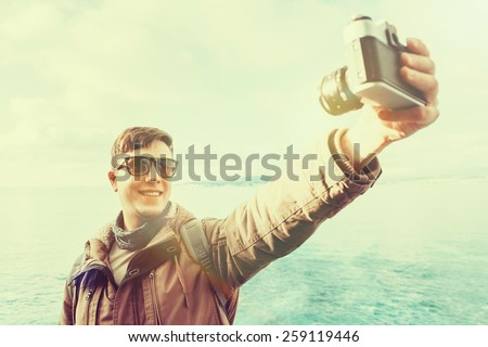 Traveler happy young man takes photographs self portrait with old photo camera on coastline on background of sea. Image with instagram filter - stock photo