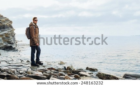 Traveler hipster young man with backpack standing on coastline near the sea with old vintage photo camera. Concept of travel and hiking - stock photo