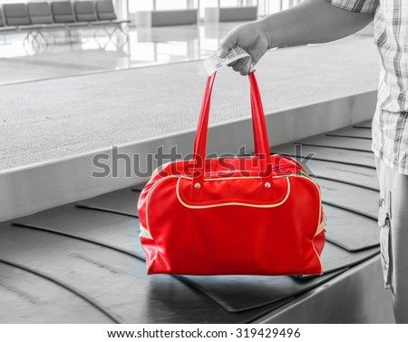 Traveler his luggage at conveyor belt in arrivals lounge of airport terminal building - stock photo
