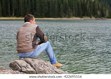 Traveler Man enjoying mountain lake view. Man looking at  horizon, loneliness concept.