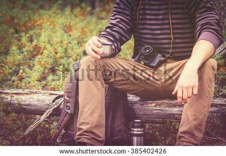 Traveler Man relaxing in forest with photo camera, backpack and thermos drinking tea Travel Lifestyle concept Summer vacations outdoor - stock photo