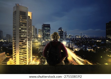 Traveler man sitting on the top of building looking at the city at night. Business travel concept - stock photo
