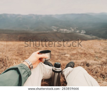 Traveler man sitting with cup of tea and thermos in the mountains. Point of view shot - stock photo