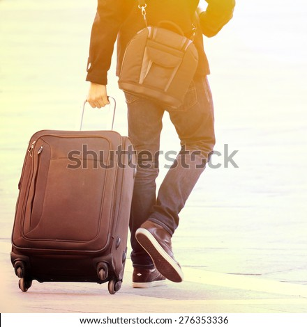 Traveler man walking with suitcase in the street - stock photo