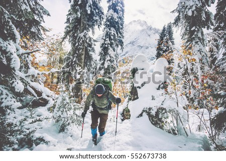 Traveler Man with backpack hiking in winter snowy forest landscape Travel Lifestyle concept adventure active vacations outdoor cold weather into the wild