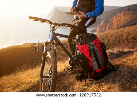 traveler on a bicycle route paves the tablet - stock photo