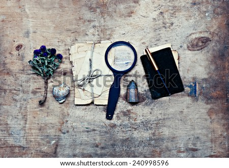 Traveler researcher notes on old wooden background - stock photo