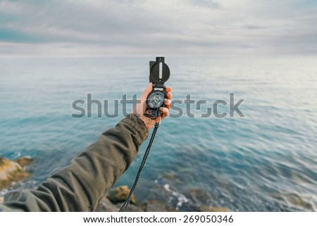 Traveler searching direction with a compass on coast near the sea in summer. Point of view - stock photo