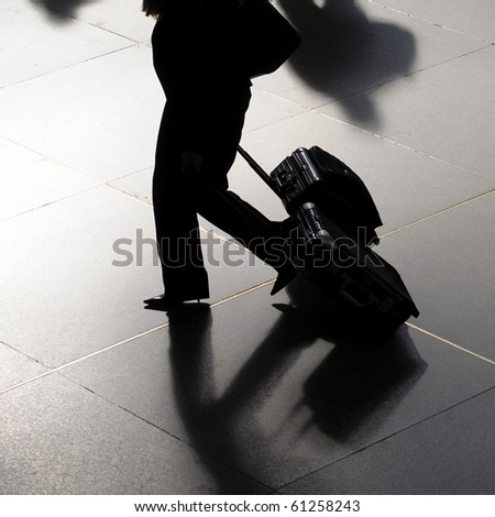 Traveler silhouette of business woman at airport walking with suitcases - stock photo