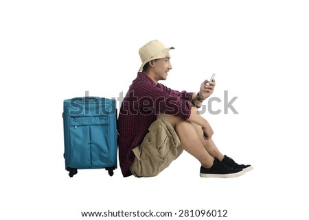 Traveler sitting against a suitcase and using a mobile phone isolated over white background - stock photo