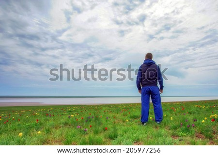 Traveler standing  in the meadow with blossoming flowers in spring