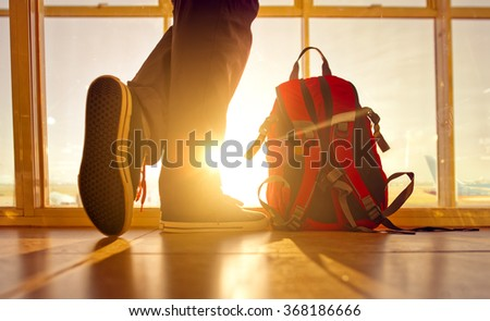 Traveler stands near the backpack at the airport, face is not visible.  - stock photo